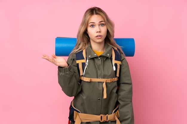Tiener bergbeklimmer meisje met een grote rugzak geïsoleerd op roze twijfels gebaar maken