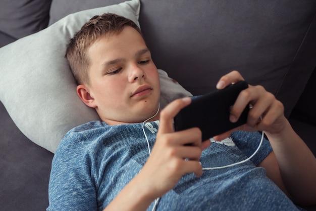 Tiener berichten naar vrienden chatten op mobiel, films kijken en spelletjes spelen op de bank in de kamer