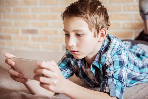 Tiener berichten naar vrienden chatten op mobiel liggend op de bank in de huiskamer
