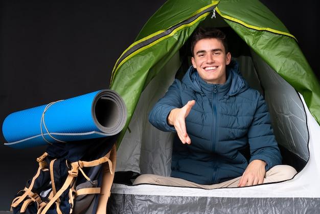 Tiener blanke man in een camping groene tent geïsoleerd op zwarte achtergrond handen schudden voor het sluiten van een goede deal