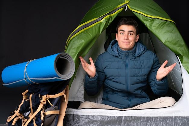 Tiener blanke man in een camping groene tent op zwarte muur met twijfels terwijl het verhogen van de handen