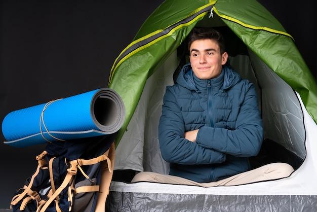 Tiener blanke man in een camping groene tent op zwarte muur
