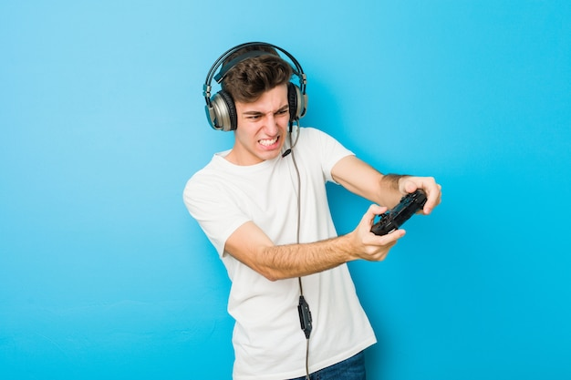 Tiener blanke man met behulp van koptelefoon en spelbesturing