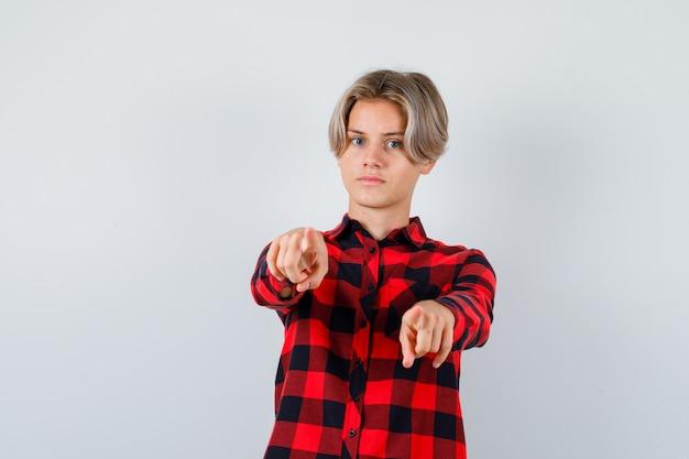 Tiener blond mannetje wijzend naar voren in casual shirt en attent, vooraanzicht.