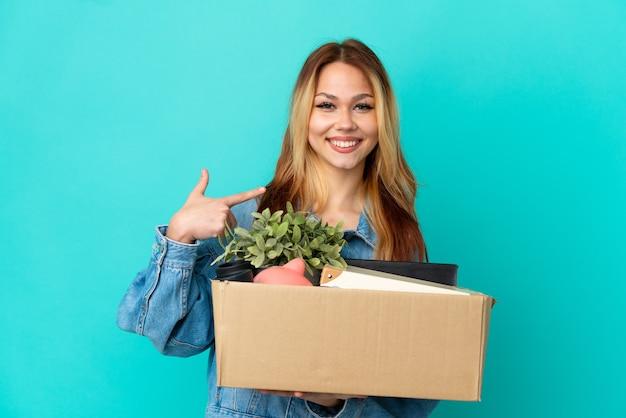 Tiener blond meisje dat een zet doet terwijl ze een doos vol dingen oppakt en een duim omhoog gebaar geeft