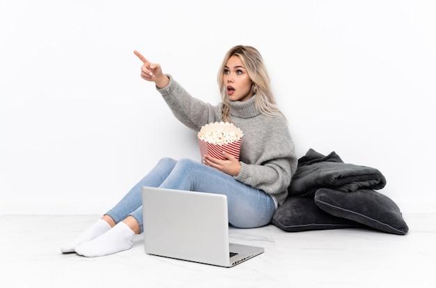 Tiener blond meisje dat popcorn eet terwijl het letten van op een film op laptop die weg richten