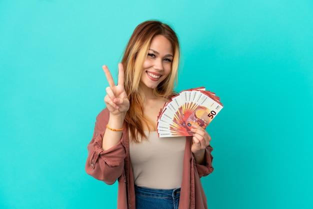 Tiener blond meisje dat veel euro's neemt over een geïsoleerde blauwe achtergrond die glimlacht en een overwinningsteken toont