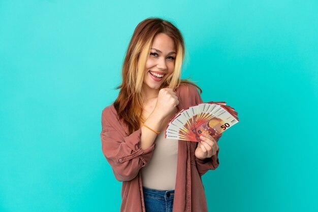 Tiener blond meisje dat veel euro's neemt over geïsoleerde blauwe achtergrond die een overwinning viert