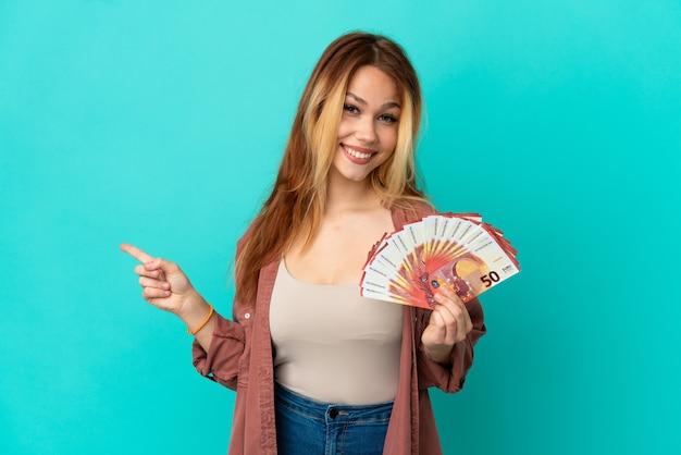 Tiener blond meisje dat veel euro's neemt over geïsoleerde blauwe achtergrond die naar achteren wijst