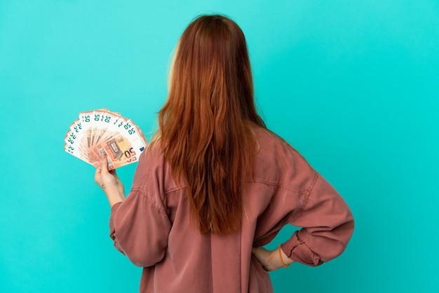 Tiener blond meisje dat veel euro's neemt over geïsoleerde blauwe achtergrond in achterpositie