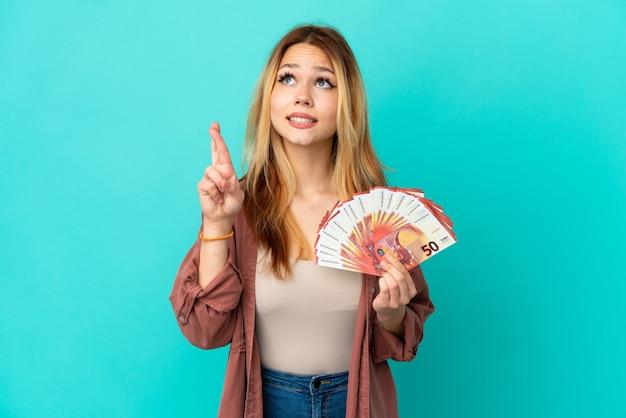 Tiener blond meisje dat veel euro's neemt over geïsoleerde blauwe achtergrond met vingers die kruisen en het beste wensen