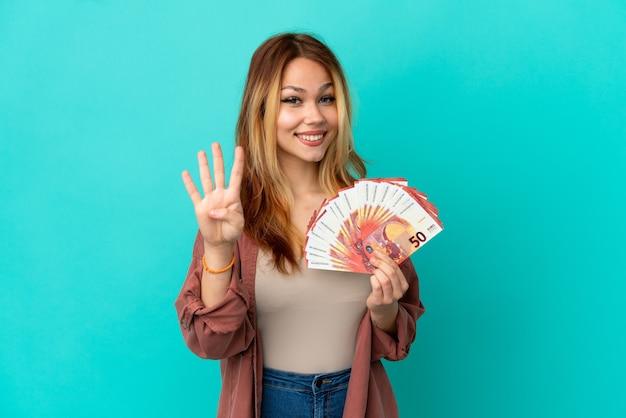 Tiener blond meisje dat veel euro's over geïsoleerde blauwe achtergrond gelukkig neemt en vier met vingers telt count