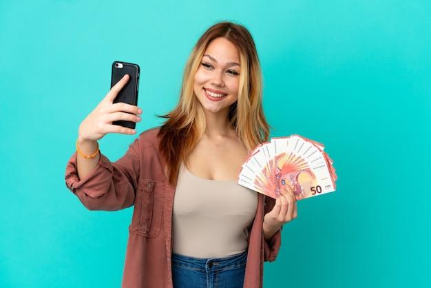 Tiener blond meisje dat veel euro's over geïsoleerde blauwe achtergrond neemt en een selfie maakt
