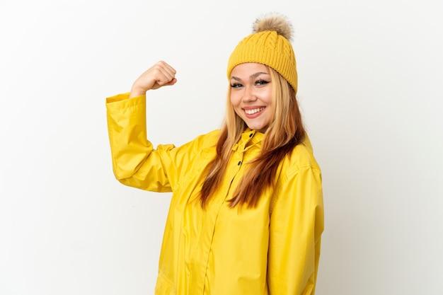 Tiener blond meisje draagt een regendichte jas over een geïsoleerde witte achtergrond die een sterk gebaar doet