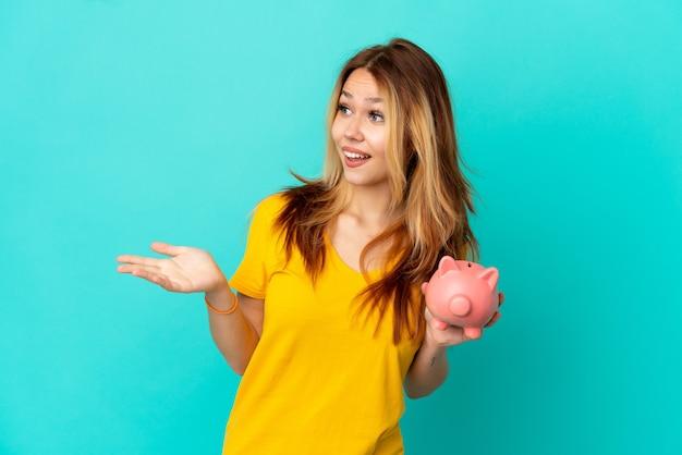 Tiener blond meisje houdt een spaarpot over geïsoleerde blauwe achtergrond met verrassingsuitdrukking terwijl ze opzij kijkt
