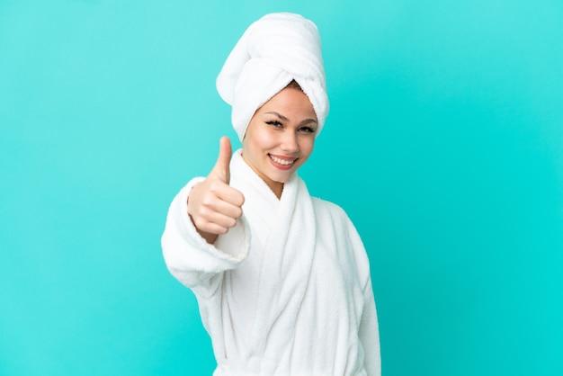 Tiener blond meisje in een badjas over geïsoleerde blauwe achtergrond met duimen omhoog omdat er iets goeds is gebeurd