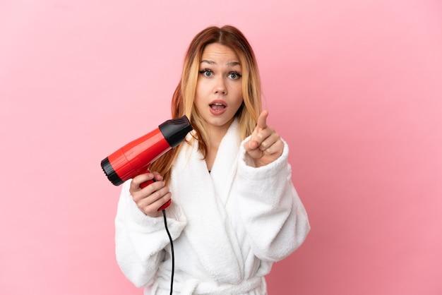 Tiener blond meisje met een haardroger over geïsoleerde roze achtergrond verrast en naar voren wijzend