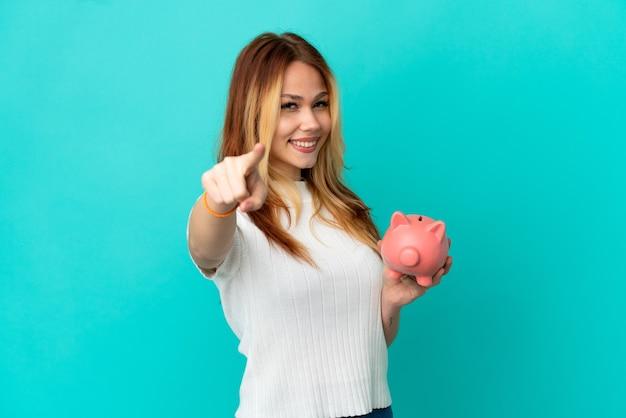 Tiener blond meisje met een spaarpot over een geïsoleerde blauwe achtergrond die naar voren wijst met een gelukkige uitdrukking