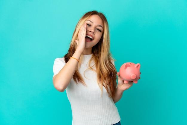 Tiener blond meisje met een spaarpot over geïsoleerde blauwe achtergrond schreeuwend met wijd open mond