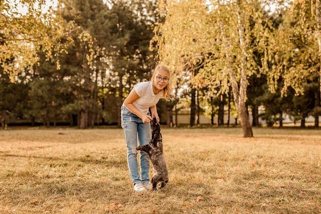 Tiener blond meisje met grote glazen lachen en spelen met kleine puppy spaniel in het warme park.