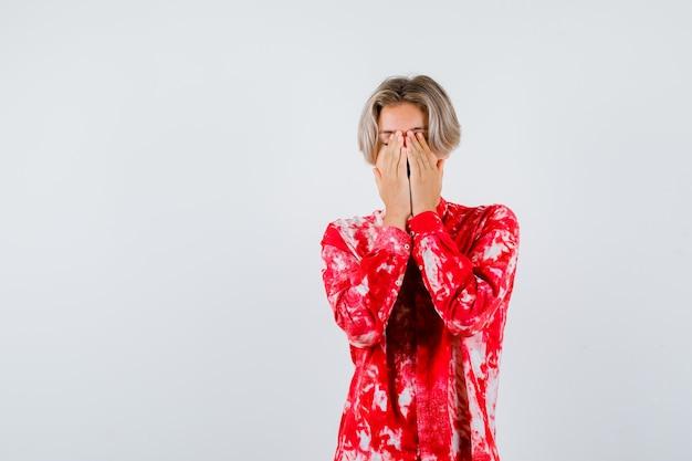 Tiener blonde man in oversized shirt dat gezicht bedekt met handen en nieuwsgierig kijkt, vooraanzicht.