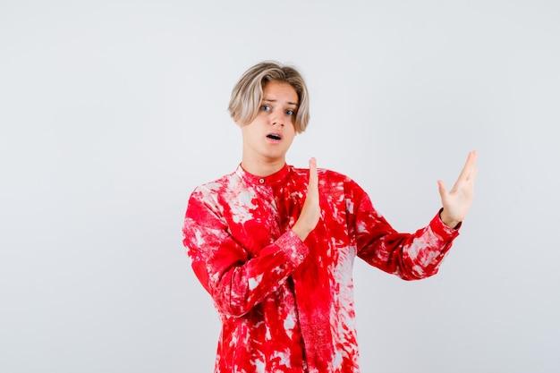 Tiener blonde man in oversized shirt met karate chop gebaar en bang, vooraanzicht.