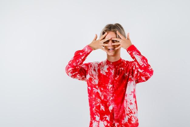 Tiener blonde man kijkt door vingers in oversized shirt en kijkt nieuwsgierig, vooraanzicht.