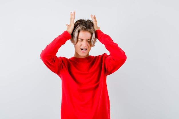 Tiener blonde man met handen op het hoofd in rode trui en op zoek verontrust. vooraanzicht.