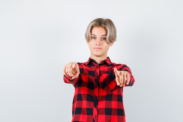 Tiener blonde man wijst naar voren in casual shirt en ziet er zelfverzekerd uit. vooraanzicht.