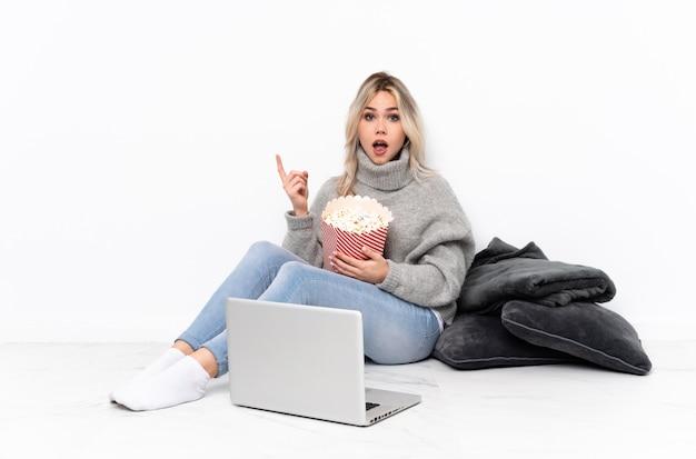 Tiener blondevrouw die popcorn eten terwijl het letten op een film op laptop verrast en richtende kant