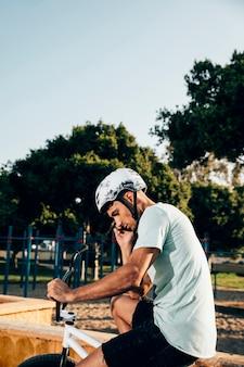 Tiener bmxruiter die zich op zijn fiets middelgroot schot bevindt