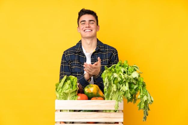Tiener boer man met vers geplukte groenten in een doos applaudisseren