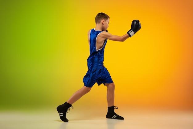 Tiener bokser tegen gradiënt neon studio achtergrond in beweging van kickboksen