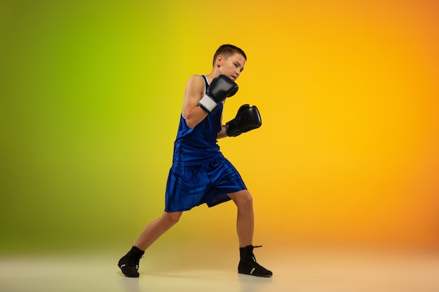 Tiener bokser tegen gradiënt neon studio achtergrond in beweging van schoppen, boksen