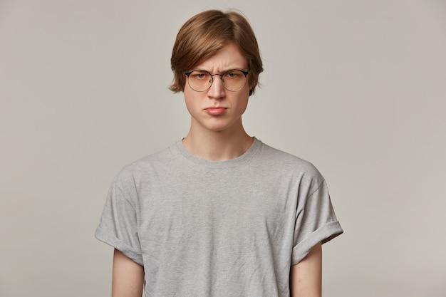 Tiener, boos uitziende man met blond haar. grijze t-shirt en bril dragen. mensen en emotie concept. fronst zijn wenkbrauwen en trekt zijn lip uit.