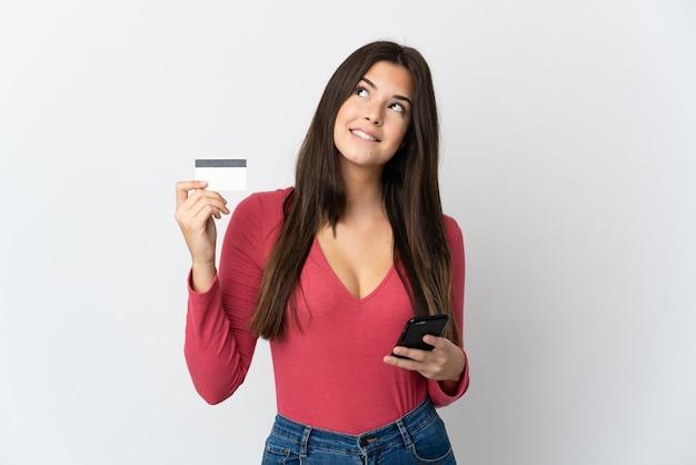 Tiener braziliaans meisje dat op wit wordt geïsoleerd dat met mobiel met een creditcard koopt terwijl het denken