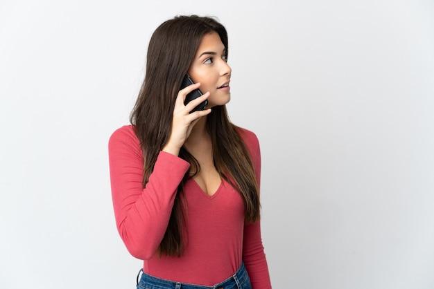 Tiener braziliaans meisje dat op witte muur wordt geïsoleerd die een gesprek met de mobiele telefoon met iemand houdt
