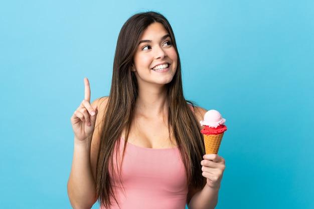 Tiener braziliaans meisje die een kornetijs over geïsoleerde blauwe achtergrond houden die de oplossing willen realiseren terwijl het opheffen van een vinger