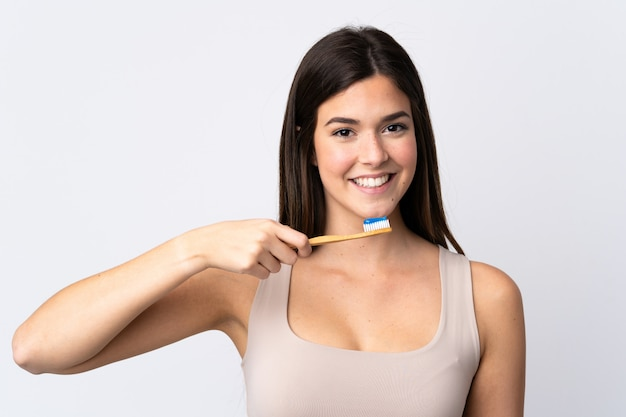 Tiener braziliaans meisje die haar tanden over geïsoleerde witte muur borstelen