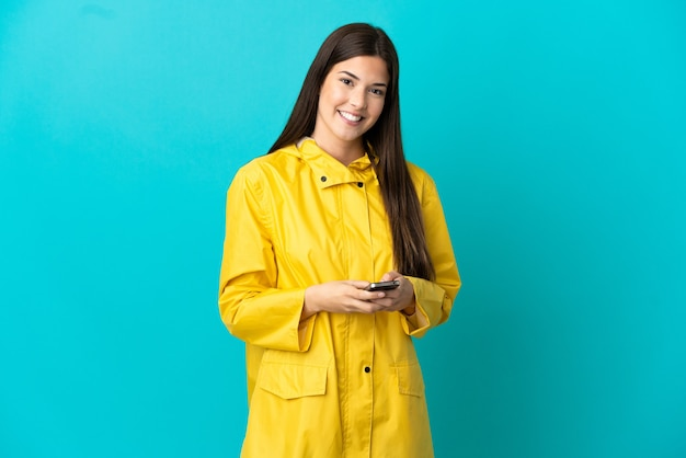 Tiener braziliaans meisje draagt een regenbestendige jas over geïsoleerde blauwe achtergrond die een bericht verzendt met de mobiel