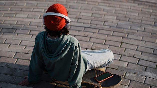 Tiener buiten luisteren naar muziek op koptelefoon zittend op skateboard