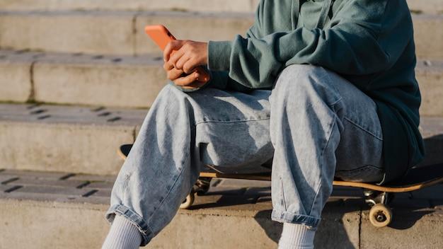 Tiener buiten zittend op skateboard en smartphone te houden