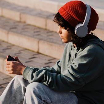 Tiener buitenshuis met behulp van smartphone en luisteren naar muziek op de koptelefoon
