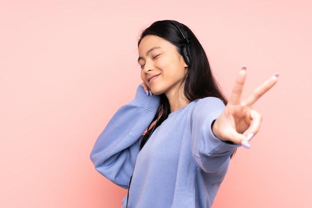 Tiener chinees meisje dat bij roze muur het luisteren muziek en het zingen wordt geïsoleerd