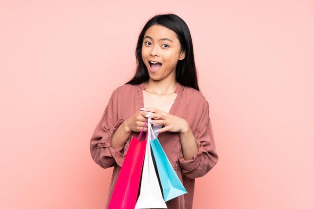 Tiener chinees meisje dat op roze wordt geïsoleerd