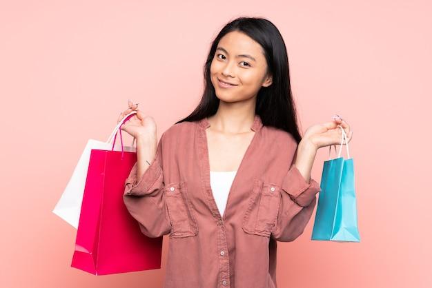 Tiener chinees meisje geïsoleerd op roze bedrijf boodschappentassen en glimlachen