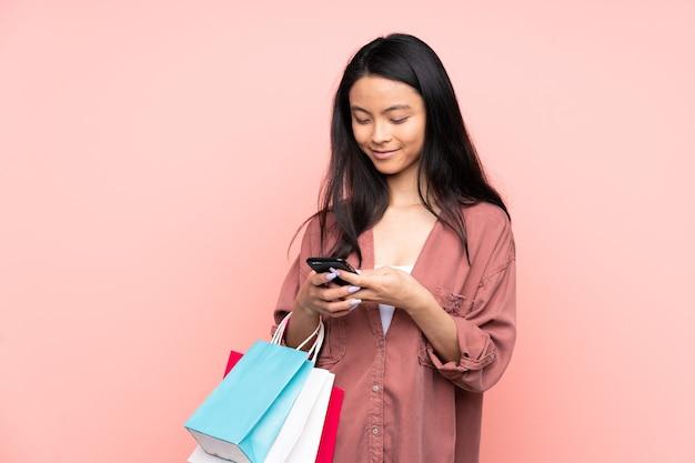 Tiener chinees meisje geïsoleerd op roze bedrijf boodschappentassen en het schrijven van een bericht met haar mobiele telefoon naar een vriend