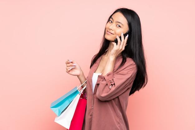 Tiener chinees meisje op roze muurholding het winkelen zakken en het roepen van een vriend met haar celtelefoon