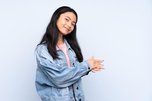 Tiener chinese vrouw bij het blauwe muur toejuichen