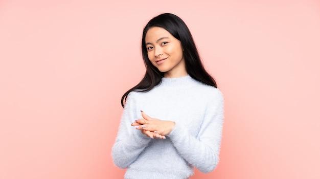 Tiener chinese vrouw bij het roze muur toejuichen na presentatie in een conferentie